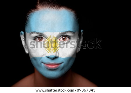 Portrait of a woman with the flag of the Argentine painted on her face. - stock photo