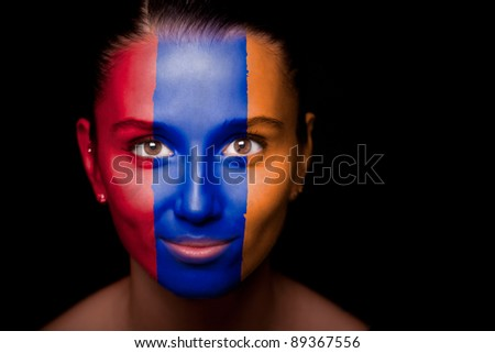 Portrait of a woman with the flag of the Armenia painted on her face. - stock photo