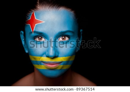 Portrait of a woman with the flag of the Aruba painted on her face. - stock photo