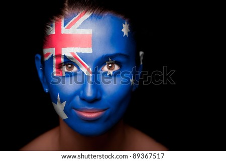 Portrait of a woman with the flag of the Australia painted on her face. - stock photo