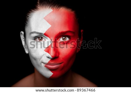 Portrait of a woman with the flag of the Bahrain painted on her face. - stock photo
