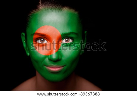 Portrait of a woman with the flag of the Bangladesh painted on her face. - stock photo