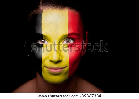 Portrait of a woman with the flag of the Belgium painted on her face. - stock photo