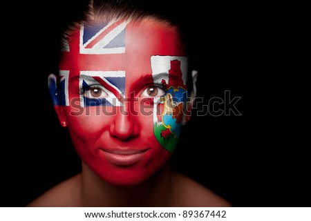 Portrait of a woman with the flag of the Bermuda Islands painted on her face. - stock photo