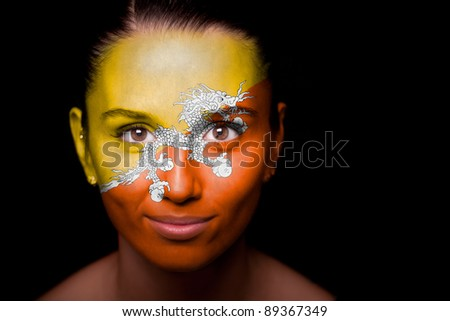 Portrait of a woman with the flag of the Bhutan painted on her face. - stock photo