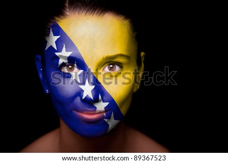 Portrait of a woman with the flag of the Bosnia and Herzegovina painted on her face. - stock photo