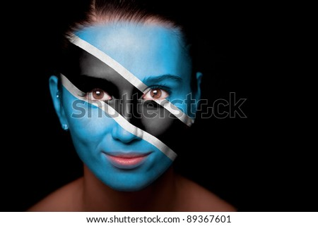 Portrait of a woman with the flag of the Botswana painted on her face. - stock photo