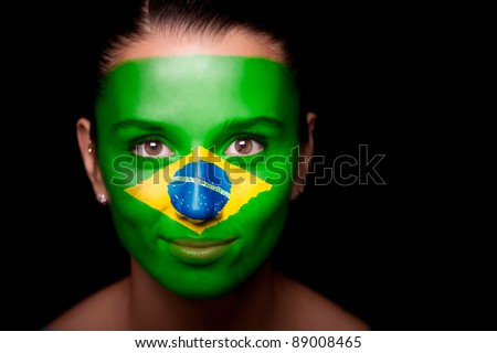 Portrait of a woman with the flag of the Brazil painted on her face.