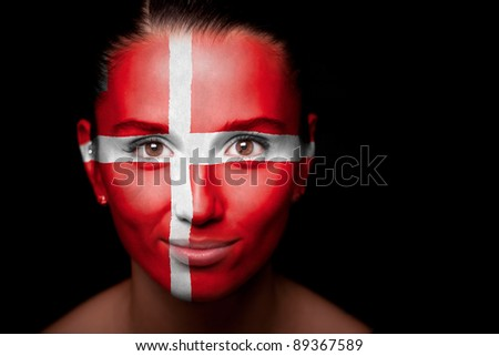 Portrait of a woman with the flag of the Denmark painted on her face. - stock photo