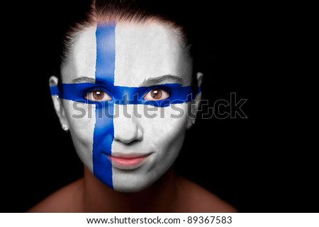 Portrait of a woman with the flag of the Finland painted on her face. - stock photo