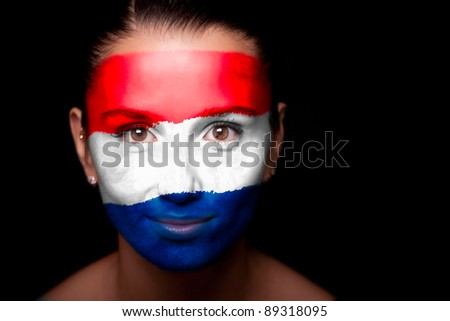 Portrait of a woman with the flag of the Netherlands painted on her face.