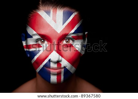 Portrait of a woman with the flag of the UK painted on her face. - stock photo