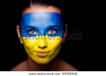 Portrait of a woman with the flag of the Ukraine painted on her face. - stock photo