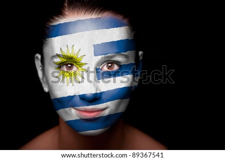 Portrait of a woman with the flag of the Uruguay painted on her face. - stock photo