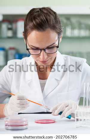 Portrait of a woman working in microbiology laboratory - stock photo