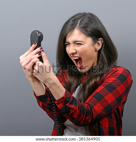 Portrait of a woman yelling at phone against gray background - stock photo