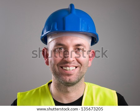 Portrait of a worker expressing positivity isolated on dark background - stock photo