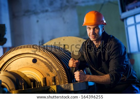 Portrait of a worker repairs powerful steam turbine. - stock photo