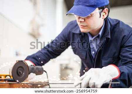 Portrait of a worker using a grinding machine to cut a metal plate - stock photo