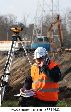 Portrait of a worker with mobile phone on a construction site - stock photo
