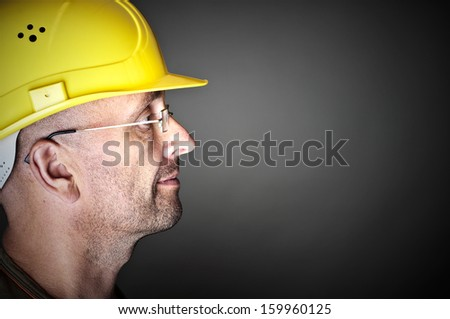 Portrait of a worker with yellow hard hat - stock photo