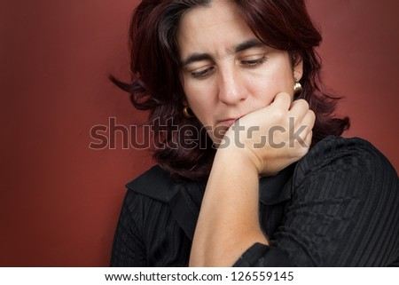 Portrait of a worried and thoughtful  woman with a dark red background