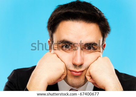 Portrait of a worried businessman, blue background