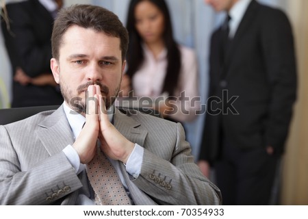 Portrait of a worried businessman with his team working behind - stock photo