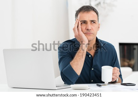 Portrait Of A Worried Mature Man With Laptop Holding Cup - stock photo