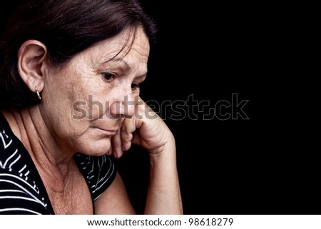 Portrait of a worried old woman with a sad expression isolated on black - stock photo