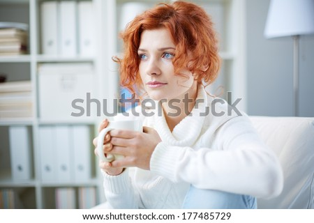 Portrait of a worried woman with cup of tea - stock photo