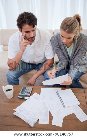 Portrait of a worried young couple doing their accounting in their living room - stock photo