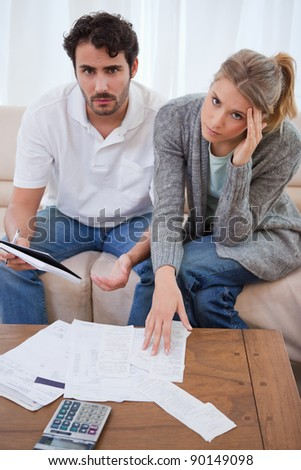 Portrait of a worried young couple looking at their bills in their living room - stock photo
