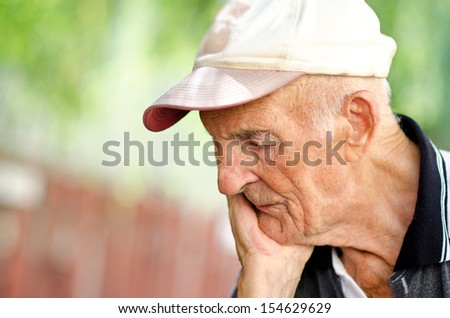 Portrait of a wrinkled and expressive old man outdoor - stock photo