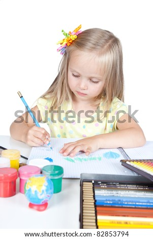 Portrait of a y happy little schoolgirl at the desk over white - stock photo