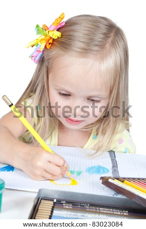 Portrait of a y happy little schoolgirl drawing at the desk over white - stock photo