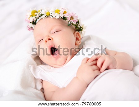 Portrait of a yawning baby girl on a light background with a wreath of flowers on her head - stock photo