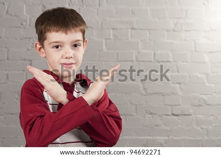 Portrait of a 10-year-old boy with crossed arms in the form X. Studio shoot. - stock photo