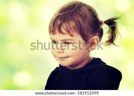 Portrait of a 2 year old girl against abstract green background