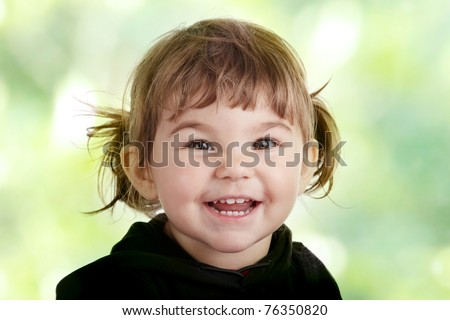 Portrait of a 2 year old girl against abstract green background - stock photo