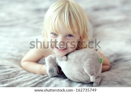 Portrait of a 2 years old child playing on his parent's bed - stock photo