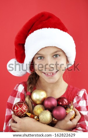 Portrait of a 7 years old child wearing Santa hat on red background