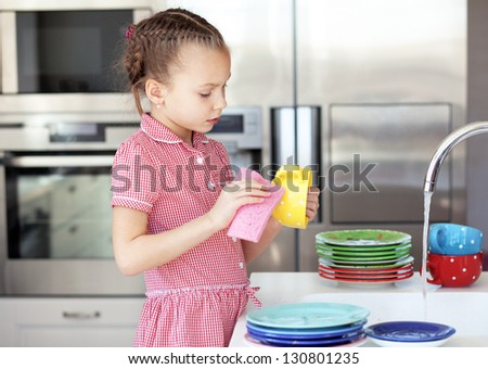 Portrait of a 6 years old girl washing the dishes at home - stock photo
