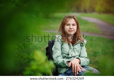 Portrait of a yong beautiful woman smiling in a wheelchair in the park. Green background. Spring day.