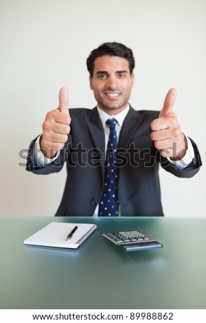 Portrait of a young accountant with the thumbs up in his office - stock photo