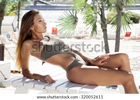 Portrait of a young adult attractive sexy and sensuality pretty beautiful brunette woman in grey bikini on the summer sunlight beach