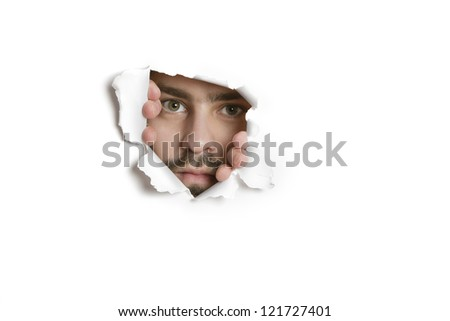Portrait of a young adult Caucasian man peeking from ripped paper hole - stock photo
