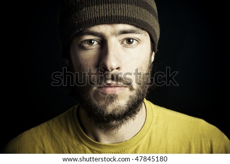 Portrait of a young adult male persone looking at camera with a serious expression. About the shot: studio shot with professional flash lights. - stock photo