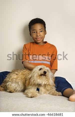 Portrait of a young African American boy sitting on the floor and petting a small dog. Vertical shot. - stock photo
