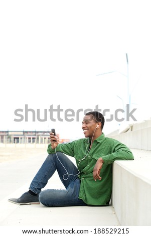 Portrait of a young african american man relaxing outdoors, listening to music on mobile phone - stock photo